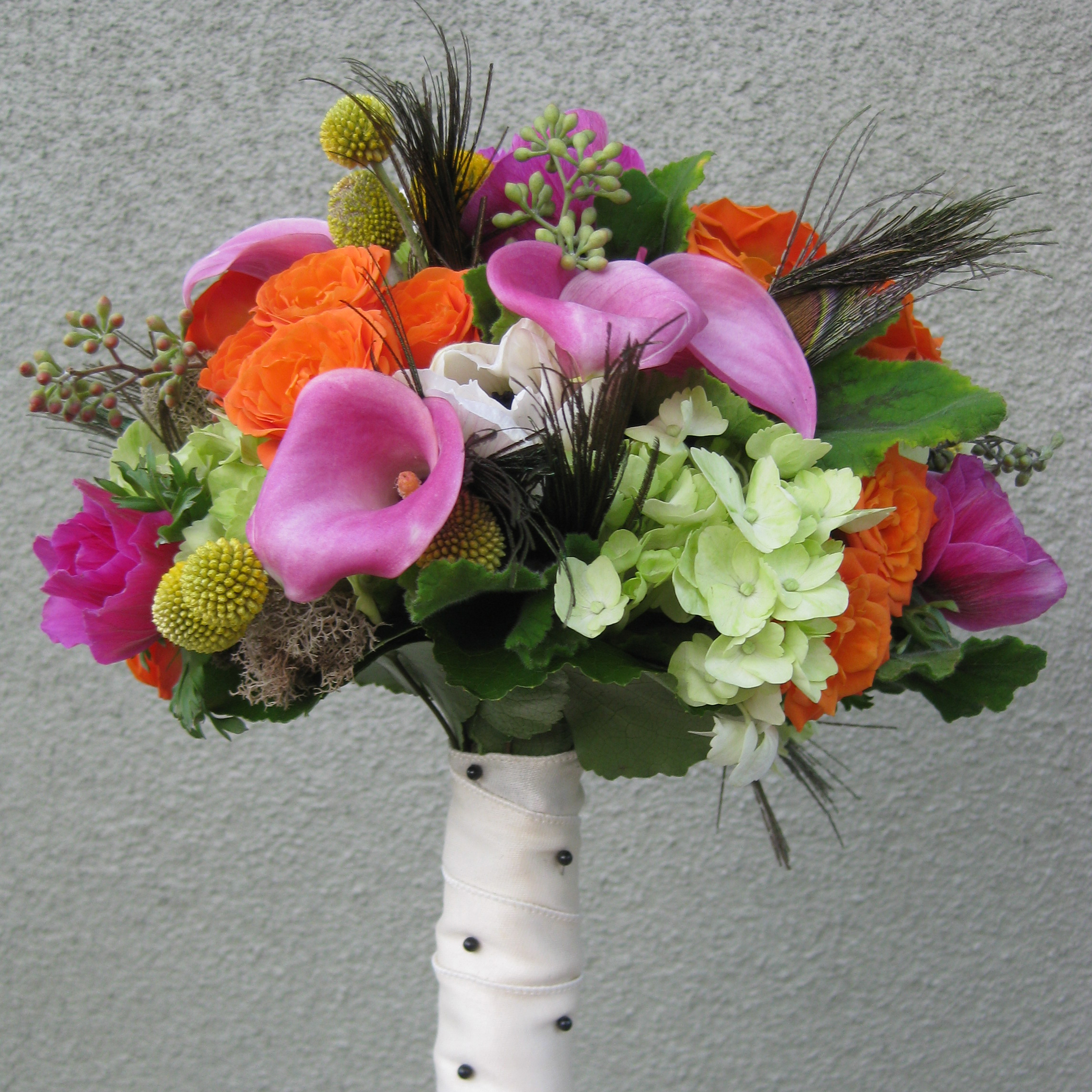 Peacock feathers are tucked low into the bouquet to add the perfect amount