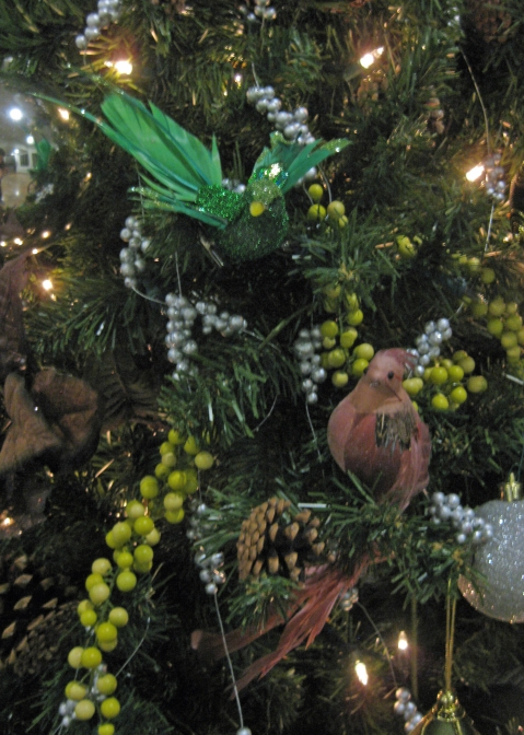 "The second tree was more of a natural inspired tree created from pinecones, birds in a pale mauve and forest green tone and a variety of ""berries"".  The top of the tree was accented with an oversized linen ribbon bow."