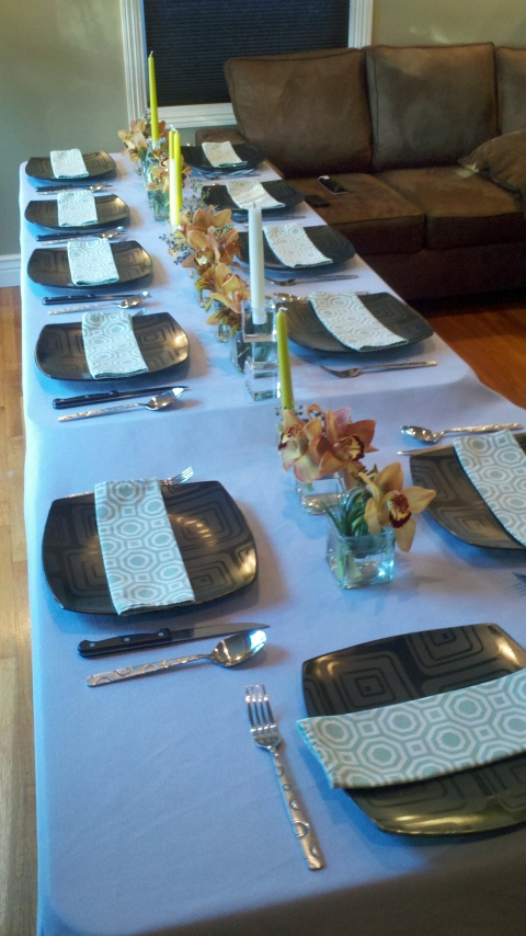 The table was decorated with a light gray table cloth, black rounded square plates, green patterned napkins, small cubes filled with copper/ brown cymbidium orchids and a few taper candles.