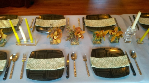 The table was decorated with a light gray table cloth, black rounded square plates, green patterned napkins, small cubes filled with copper/ brown cymbidium orchids and a few taper candles