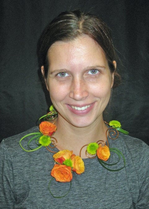 We used aluminum wire in copper with lily grass, green button mums, orange spray roses and lemon leaf to create a necklace, boutonniere and a wrist corsage. The majority of the pieces were glued however I still find it important to go over wire and taping techniques.