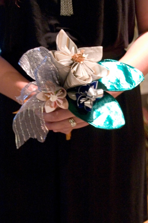 . I did not want to do a bouquet with the ribbons attached to the paper plate so I created origami flowers from the wrapping paper from the shower. I used the ribbons underneath the bouquet as well as in the center of the flowers.  I got slightly carried away making flowers and made too many! So instead of wasting them I made small bouquets for the bridesmaids. Each was slightly different since all of us girls were going to be wearing different colors.